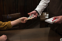 Man taking payment from woman at restaurant