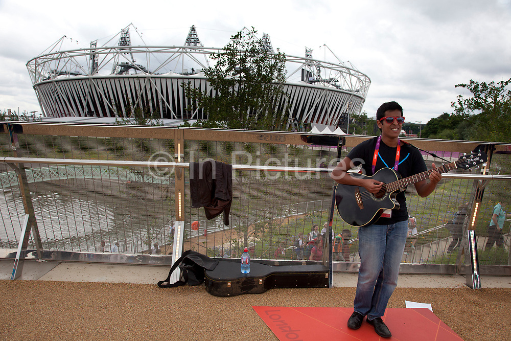 London 2012 Olympic Park in Stratford, East London. Local musicians provide some entertainment on site. This singer and guitar performs to tha backdrop of the Olympic stadium.