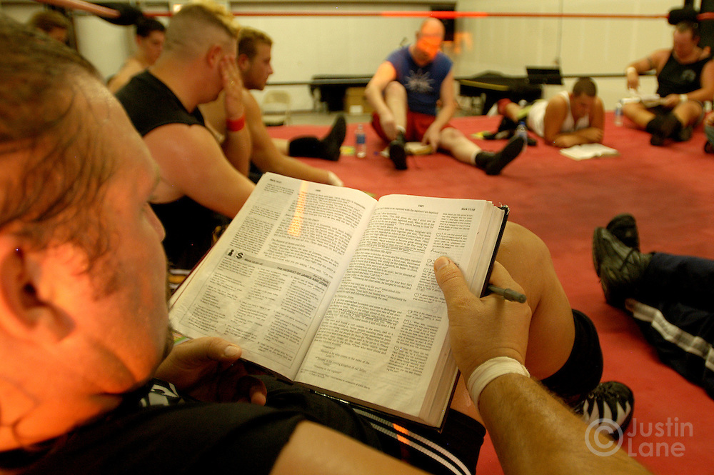 Tim Scoggins (L), of the Christian Wrestling Federation, reads his bible during bible study following the group's regular practice in Rockwall, TX Monday, July 18, 2005. The group uses wrestling to minister to people who are interested in the sport but have not yet found Jesus. The group has been ministering since 2000.