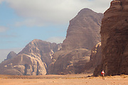 A young man explores the desert by foot in Wadi Rum, Jordan.