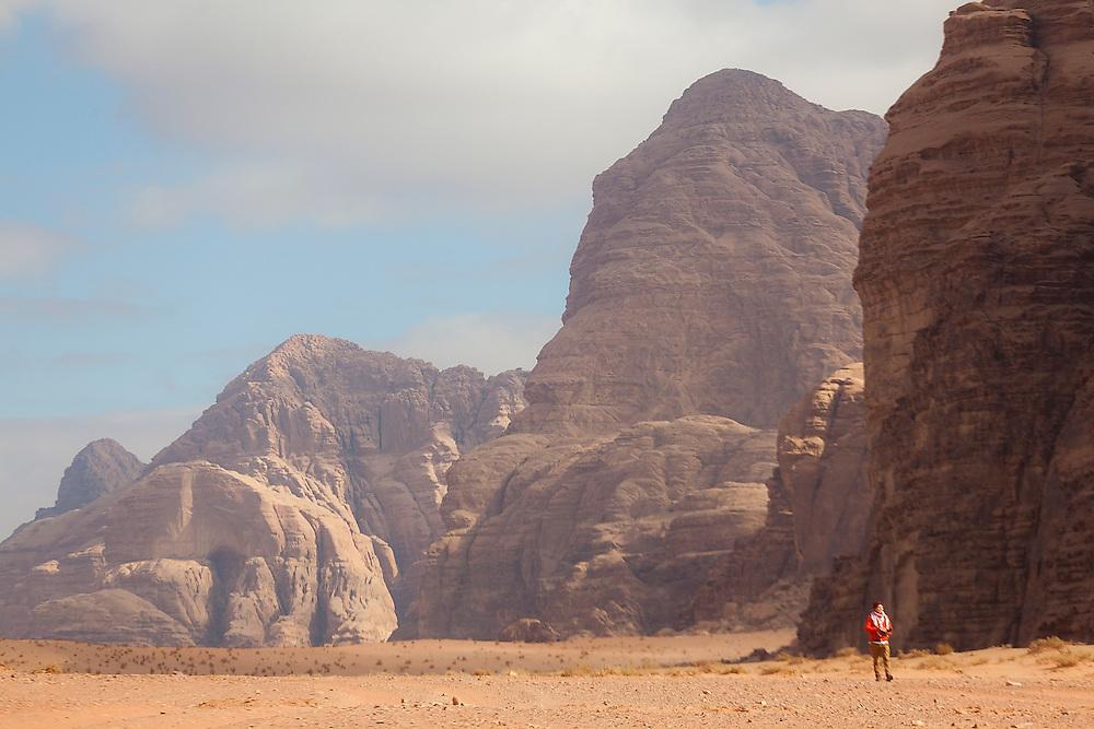 A young man explores the desert by foot in Wadi Rum, Jordan.