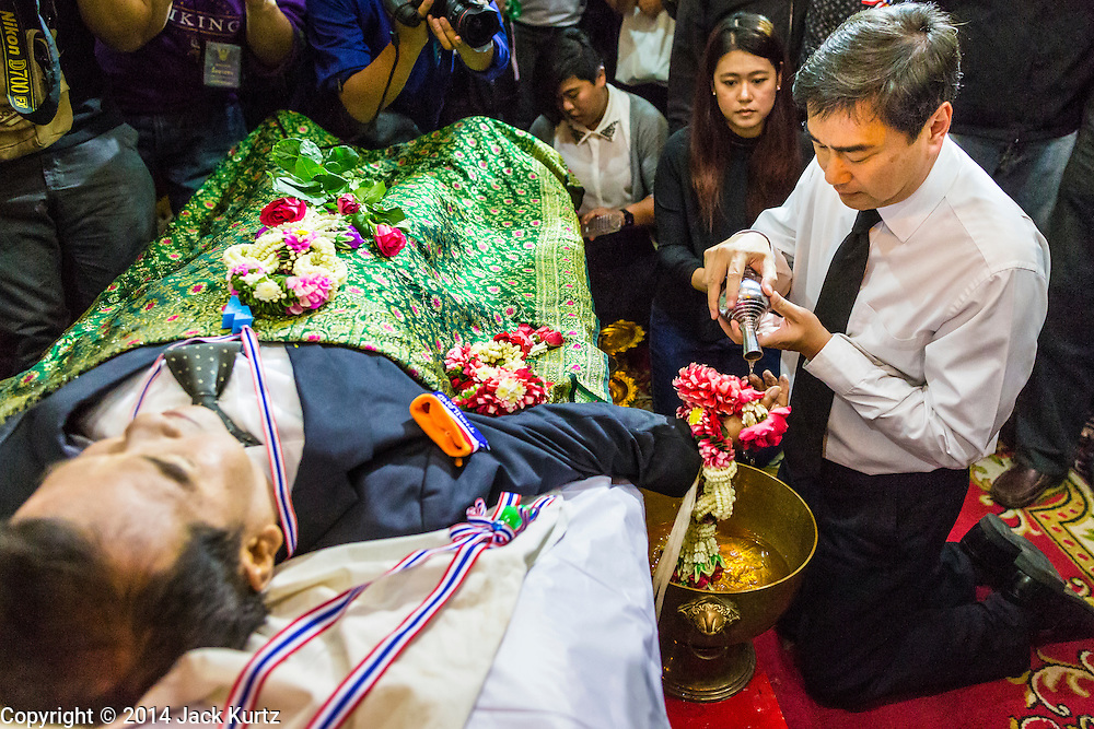 27 JANUARY 2014 - BANGKOK, THAILAND: ABHISIT VEJJAJIVA, former Prime Minister of Thailand and a leader of the anti-government movement washes the hand of his friend and colleague Suthin Taratin during bathing rites for murdered anti-government leader at Wat Sommanat Rajavaravihara in Bangkok. In Thai tradition, after death a bathing ceremony takes place in which relatives and friends pour water over one hand of the deceased. Suthin was a core leader of the People's Democratic Force to Overthrow Thaksinism (Pefot), one of several organizations leading protests against the elected government of Thai Prime Minister Yingluck Shinawatra. He was murdered Sunday, Jan. 28, while he was leading a rally to prevent voters from reaching a polling center in the Bang Na district of Bangkok.     PHOTO BY JACK KURTZ