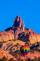 Hot air balloon flying in front of Church Rock during the Red Rock Balloon Rally, Red Rock State Park, near Gallup, New Mexico USA.