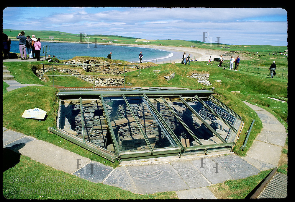 Visitors walk atop grassy mounds looking down into 5000-year-old ruins of Skara Brae; Orkney Is. Scotland