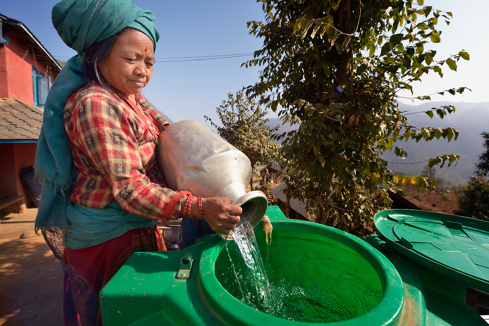 A woman pours water into a cistern at her home in Salang, a village in the Dhading District of Nepal where Dan Church Aid, a member of the ACT Alliance, has provided a variety of support to local villagers in the wake of a devastating 2015 earthquake. The village's water system was destroyed by the quake, forcing women to walk two hours or more to a nearby river to fetch water. Working with a local organization, the Forum for Awareness and Youth Activity, the ACT Alliance rebuilt the village's water system.