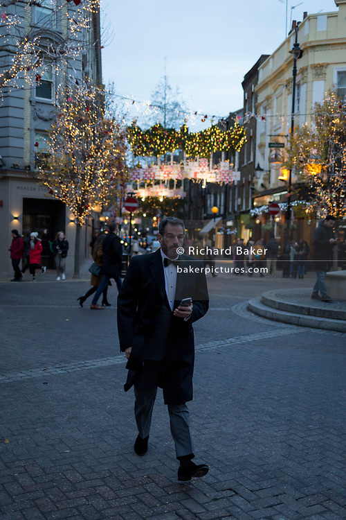 A man wearing a bow tie walks through Seven Dials near Covent Garden, on 12th December 2017, in London England.