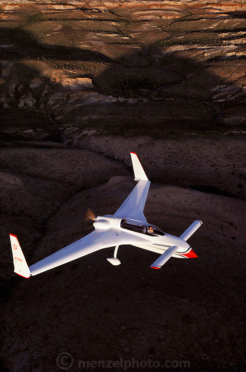 "Long-EZ flying above the Mojave desert in California. The aircraft is of an unusual design, having forward-mounted ""canard"" wings instead of a tail plane and a rear-mounted ""pusher"" propeller. The canard makes the plane virtually stall proof. It has a slightly steeper tilt than the regular wing; thus the canard begins to stall before the main wing, and as it does so, it drops the nose and gains speed. The Long-EZ has a range of up to 7700 kilometers, a ceiling of 27,000 feet (8230 meters) and a top speed of 309 kilometers per hour. The aircraft is available in a kit form, manufactured by the Rutan Aircraft Factory, which can be assembled in as few as 1000 hours."