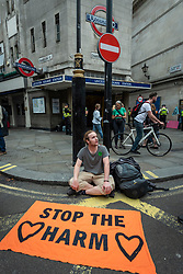 © Licensed to London News Pictures. 23/08/2021. LONDON, UK.  A protester sits in front Leicester Square tube station as climate activists from Extinction Rebellion stage a protest in Covent Garden.  The group has announced that it will stage protests in the capital for the next two weeks as they try to raise awareness of the effects of big business on climate change.  Photo credit: Stephen Chung/LNP