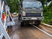 09 AUGUST 2018 - KAENG KRACHAN, PHETCHABURI, THAILAND:  A Thai army truck on a water covered rural road brings soldiers in to work with a construction crew working on an emergency spillway for the Kaeng Krachan Dam. The Phetchaburi River flows from Kaeng Krachan Dam to the Gulf of Siam through several towns including Ban Lat, Phetchaburi (the capital of Phetchaburi province) and Ban Laem. Government officials have warned residents of those towns that their towns will flood because the reservoir behind the dam is approaching capacity. Ban Lat and Phetchaburi could be flooded for several weeks. Residents of Ban Laem have been warned that their community could be inundated for over a month. Dams in Kanchanaburi province, west of Phetchaburi, are also approaching capacity and flooding is also expected in that area.  PHOTO BY JACK KURTZ