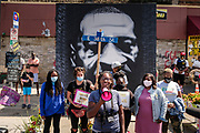 "15 AUGUST 2020 - MINNEAPOLIS, MINNESOTA:  Women rally in front of a large portrait of George Floyd in front of Cup Foods at the George Floyd Memorial in Minneapolis. Floyd, an unarmed Black man, was killed by Minneapolis police officers of May 25 in front of Cup Foods, a convenience store at the intersection of 38th and Chicago Ave. His killing sparked a week of violent protests across the country. The intersection where he was killed is still closed and has become an unofficial memorial visited by hundreds of people every day. Saturday, more than 100 people gathered at the memorial to demand the city preserve the memorial. On Saturdays in August, the intersection has a market, with venders selling Afro-centric merchandise. The city of Minneapolis had planned to start reopening the intersection as soon as Monday Aug. 17, but delayed those plans indefinitely on Friday, Aug. 14. City residents have created a ""George Floyd Zone"" at the intersection. They're demanding the recall of Hennepin County Attorney Mike Freeman, requiring Minneapolis police officers have their own private liability insurance, and the allocation of funds for businesses and residents in the community. The city is considering officially renaming Chicago Ave. between 37th and 39th ""George Floyd Jr. Place.""    PHOTO BY JACK KURTZ"