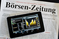 Google Nexus tablet computer running android operating system with stock market data on screen and German financial newspapers