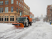 17 JANUARY 2020 - DES MOINES, IOWA: City snow removal equipment on Locust Street in Des Moines with the Iowa State Capitol in the background. The second significant snow fall in a week hit central Iowa Friday. The snow started falling during the morning rush hour and by early afternoon about five inches had fallen in Des Moines. Meteorologists said up to 1/10 of an inch of ice could cover the snow by the end of the day. The snowstorm was expected to turn into a blizzard in northern Iowa on Saturday with wind speeds above 30MPH. Many businesses in the Des Moines area closed early Friday and several of the Democratic presidential candidates cancelled their campaign events because of the snow.  PHOTO BY JACK KURTZ