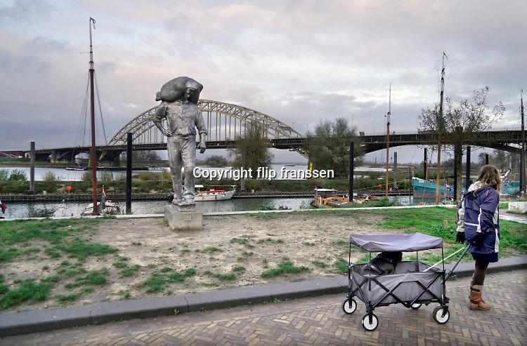 Nederland, Nijmegen, 16-11-2020 Straatbeelden van deze stad in Gelderland . Hety beeld de Kaajsjouwer van Margriet Hovens staat sinds kort aan de Lindenberghaven, het verlengde van de waalkade . Het is een ode aan de mannen die in vroeger tijden lading stukgoed van de binnenschepen haalden en aan wal brachten . De nijmeegse schrijver Frank Antonie van Alphen initieerde dit initiatief . Foto: ANP/ Hollandse Hoogte/ Flip Franssen