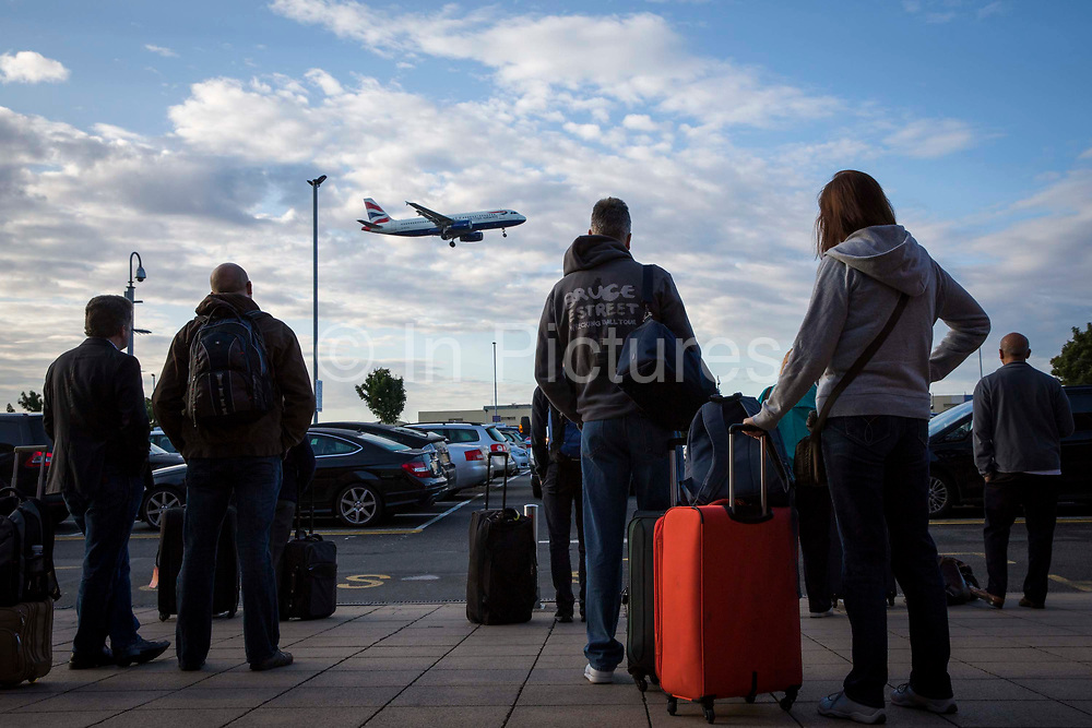 Travellers with their suitcases wait outside the Heathrow Premier Inn for the terminal shuttle bus to take them  to their required terminal at Heathrow airport.