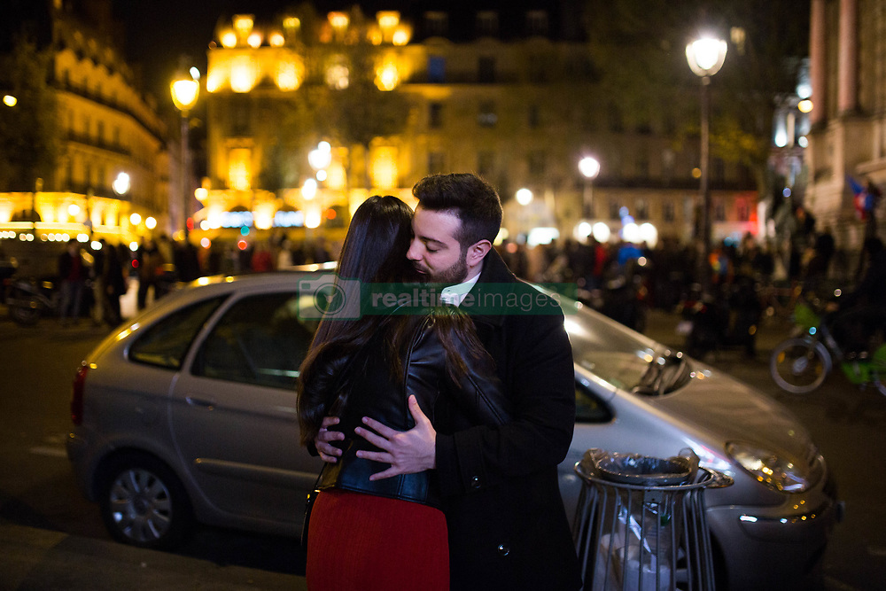 """A couple is hugging on the place saint michel next to a statue of Virgin Mary during an evening of prayer and songs organized by Catholics community the day after Notre Dame Cathedral blaze with a march organized from Saint-Sulpice church to Saint Michel and finally next to Notre Dame Cathedral in Paris early on April 16 the day after the beginning of the fire , 2019. A huge fire that devastated Notre-Dame Cathedral is """"under control"""", the Paris fire brigade said early on April 16 after firefighters spent hours battling the flames. Photo by Raphael Lafargue/ABACAPRESS.COM"""