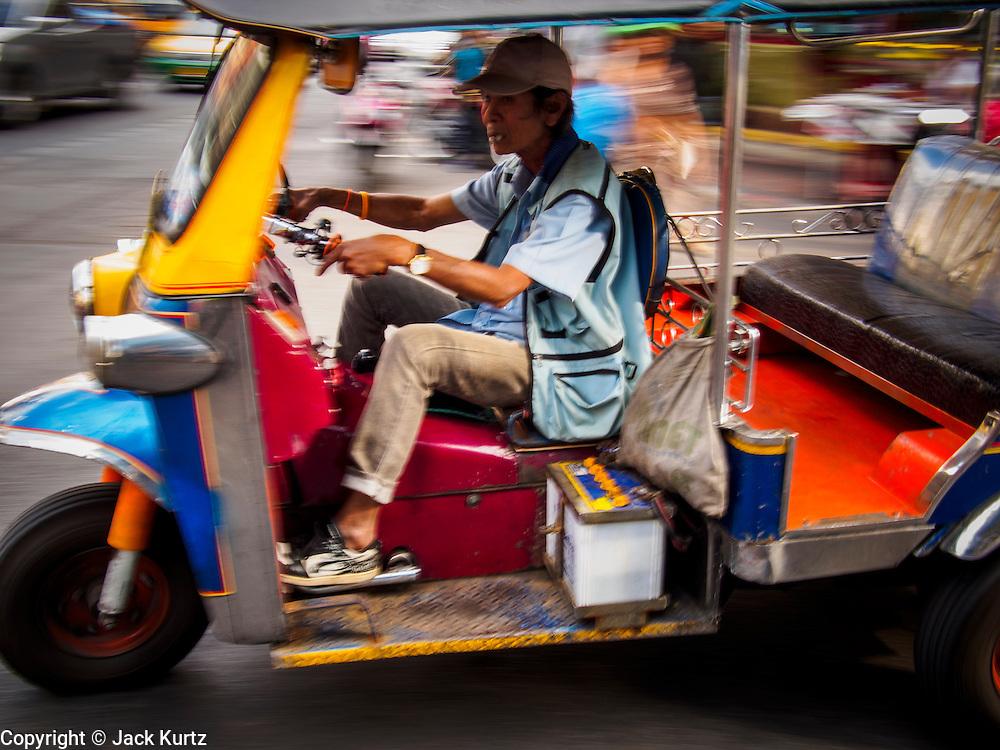 19 DECEMBER 2013 - BANGKOK, THAILAND:   A tuk-tuk or three wheeled taxi speeds through traffic in the Chinatown section of Bangkok.      PHOTO BY JACK KURTZ