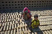 Indian woman with grandchild drying bricks made from clay at Khore Bricks Factory, Rajasthan, Northern India