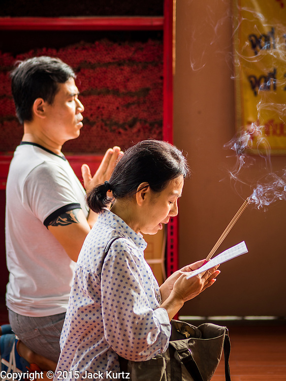 28 AUGUST 2015 - BANGKOK, THAILAND: A woman prays at the Poh Teck Tung Shrine in Bangkok's Chinatown on Hungry Ghost Day. Mahayana  Buddhists believe that the gates of hell are opened on the full moon of the seventh lunar month of the Chinese calendar, and the spirits of hungry ghosts allowed to roam the earth. These ghosts need food and merit to find their way back to their own. People help by offering food, paper money, candles and flowers, making merit of their own in the process. Hungry Ghost Day is observed in communities with a large ethnic Chinese population, like Bangkok's Chinatown.     PHOTO BY JACK KURTZ