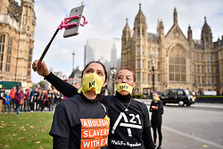 "© Licensed to London News Pictures. 14/10/2107. London, UK. Women prepare to take part in the ""The Walk For Freedom"", marching around the capital demonstrating against modern slavery.  The protest is co-ordinated with other walks which abolitionist group A21 is staging in 400 cities around the world on the same day. The facemasks represents the silence of modern slaves. Photo credit : Stephen Chung/LNP"