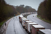 Freight torries line up in queues contained in Operation Stack on the M20 motorway at Ashford, Kent, United Kingdom on the 23rd of December 2020. Truck drivers have been waiting in operation stack on the M20 motorway for over 48 hours now, France closed it's boarders with the UK after a new faster spreading strain of the COVID-19 virus broke out in Kent.