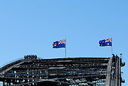 A New South Wales State Flag and an Australian Flag flying atop the arch of the Sydney Harbour Bridge. Groups of tourists can be seen climbing the bridge. Sydney, Australia
