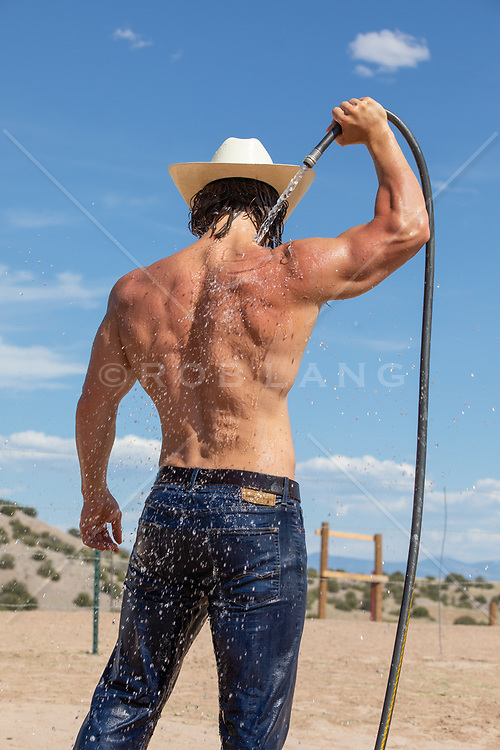 back of a cowboy hosing off with water