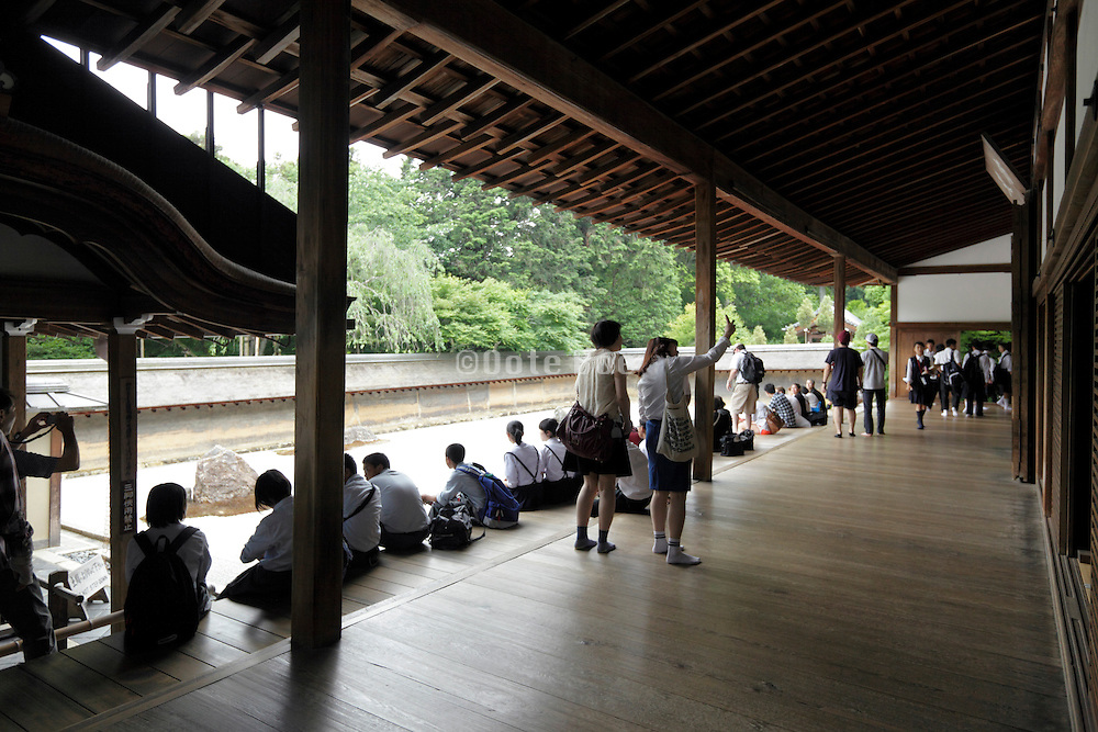 tourists and students at the Ryoanji Temple zen garden in Kyoto