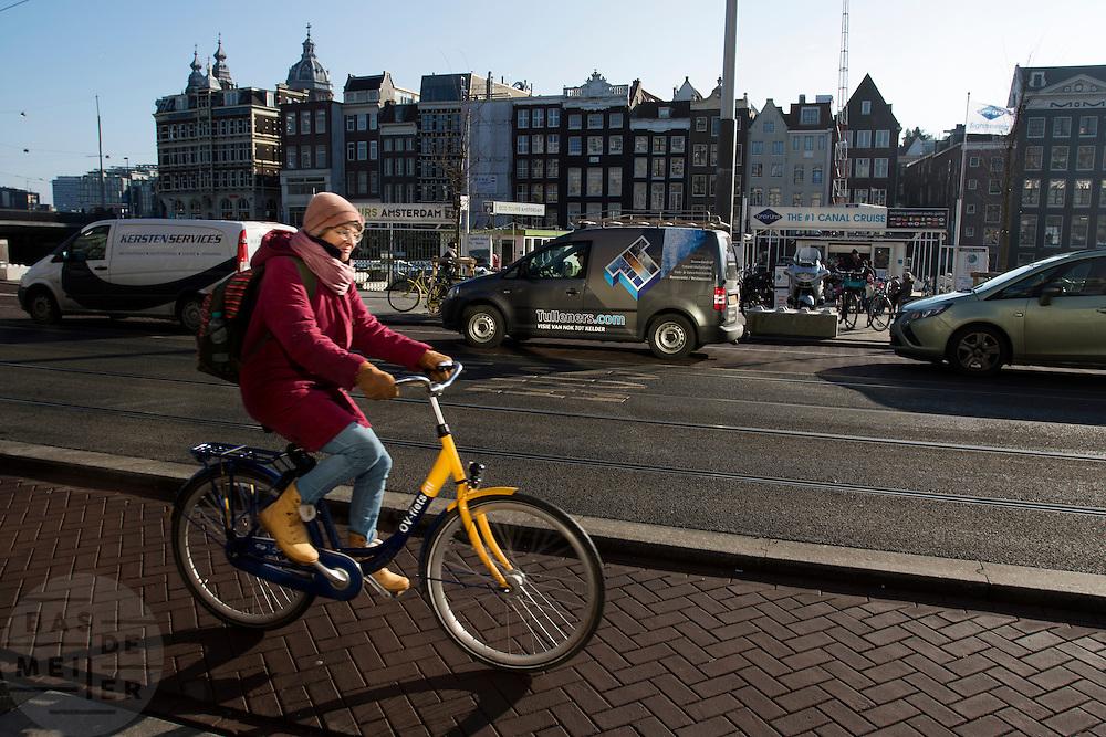 In Amsterdam rijdt een vrouw op een OV-fiets, de huurfiets van de NS, over het Damrak.<br /> <br /> In Amsterdam a woman is riding an OV-bike, the rental bike of the Dutch railways, at the Damrak.