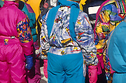 Lady skiers wearing bright thermal layers watch a local downhill competition on the slopes at Zauchensee, Austria