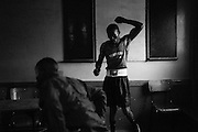 NAIROBI, KENYA - NOVEMBER 17, 2011: Kamau Ng'ang'a (right) prepares for an Olympic Qualifying boxing bout. As a Kikuyu, Ng'ang'a represents the tribe that was targeted most violently during the post-election violence of 2008. Despite his tribal affiliation, Ng'ang'a is the club favorite and hopes to represent the Kibera Olympic Boxing Club in the 2012 Olympics.<br />