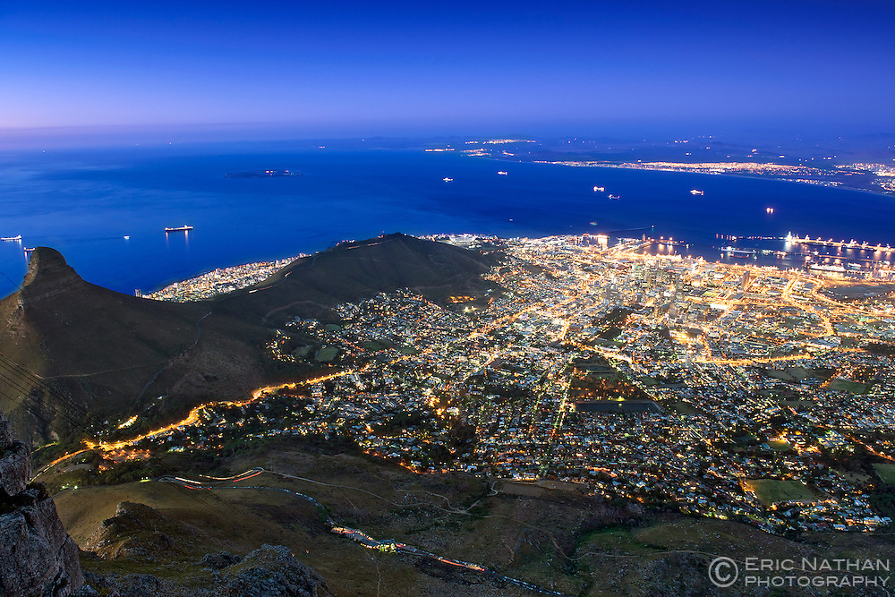 Dusk view of the city of Cape Town showing Table Bay, Robben island, Lion's Head (left) and Signal Hill (centre) seen from the summit of Table Mountain.