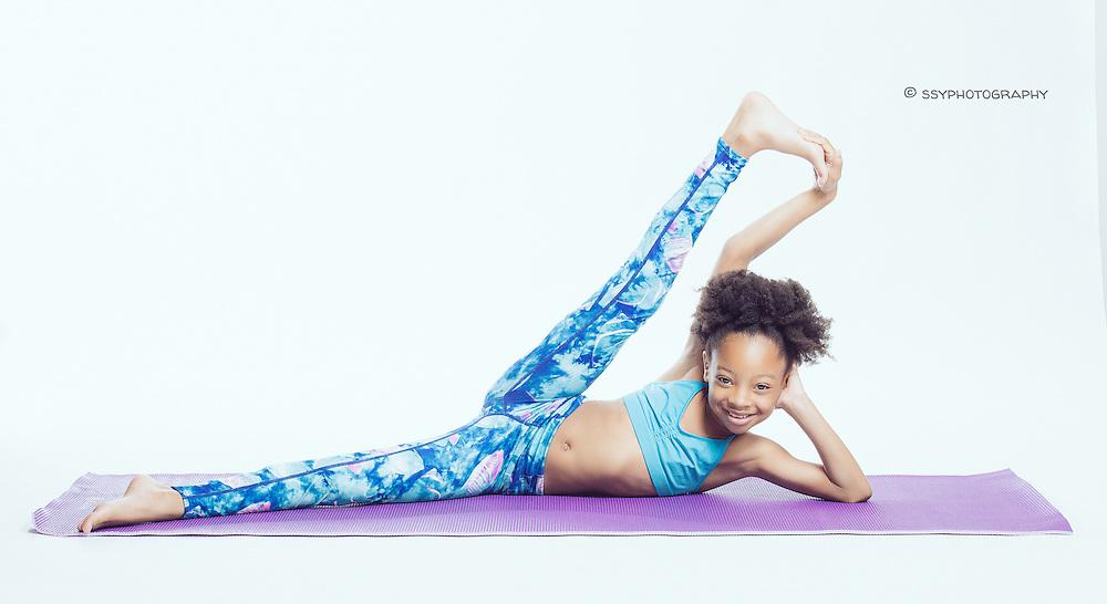 Little African American girl doing yoga on a purple yoga mat.
