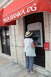 Tourist using ATM, Kotor, Montenegro, July 2018