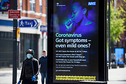 © Licensed to London News Pictures. 11/04/2020. WATFORD, UK. A man wearing a facemask walks by an advertising screen on a bus stop shelter in Watford shopping centre on Easter Saturday during lockdown as the coronavirus (COVID19) pandemic continues.  The screen shows a message by the NHS instructing the public how to react if they have coronavirus symptoms.  Photo credit: Stephen Chung/LNP