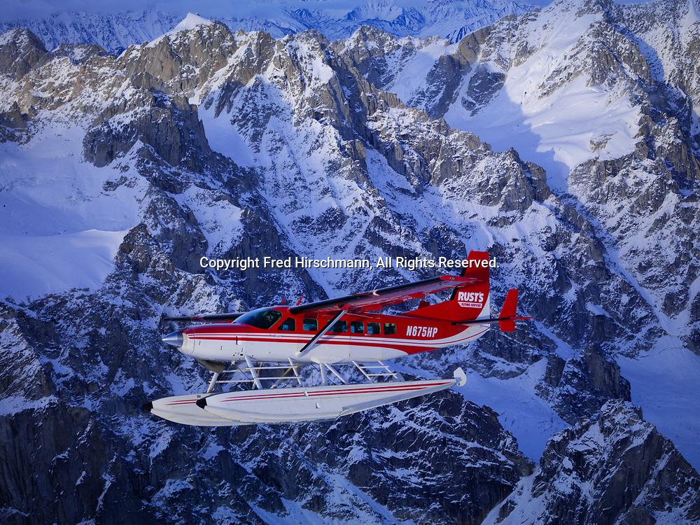 Rust's Flying Service Cessna Caravan on floats flying above the Alaska Range in Denali National Park, Alaska.