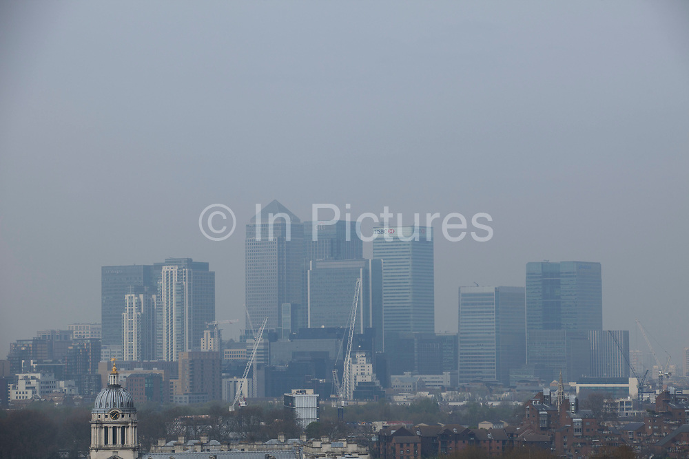 London, UK. Wednesday 2nd April 2014. Industrial pollution from Europe and dust from the Sahara region creates a layer of smog over the City of London. Barely visible through the poplluted air, the buildings seem to disappear into the poor air quality. View from Greenwich Park towards the skyline at Canary Wharf financial district.