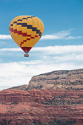 United States, Arizona, Sedona, hot air balloon in sky above red rock cliffs