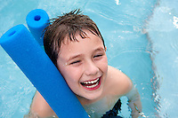 Happy boy in the swimming pool, very cheerful with swimming noodle.