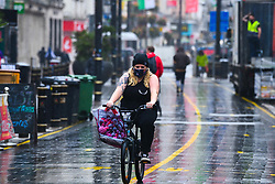 © Licensed to London News Pictures. 23/10/2020. Cardiff, UK. A girl on a bike rides down St Mary's Street in the city centre of Cardiff on the day that the Welsh Goverment's seventeen-day-long, 'Firebreak Lockdown' comes into action to try and control the spread of coronavirus across Wales. Photo credit: Robert Melen/LNP