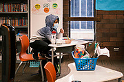 17 FEBRUARY 2021 - DES MOINES, IOWA: A fourth grade student sits by himself at Walnut Street School in downtown Des Moines. Des Moines Public Schools (DMPS) opened to in person education this week after teaching most of the 2020-2021 school year either remotely or with a hybrid/remote learning model. Elementary school classrooms, which used to sit 2-4 students at a table, have gone to individual desks, placed 6 feet apart, in classrooms. Students are required to wear masks for most class activities. The district has ended its hybrid model. The Governor of Iowa has aggressively pushed schools to return to in person education, going so far as to threaten to withhold funds from districts that don't return to in person classes. DMPS, the largest school district in Iowa, has resisted the Governor's push because Polk County, IA, has been a Coronavirus/COVID-19 hotspot with positivity rates well above 10 percent. The district was recently able to vaccinate many teachers and positivity rates have fallen to 9 percent, making it safer to reopen schools.    PHOTO BY JACK KURTZ