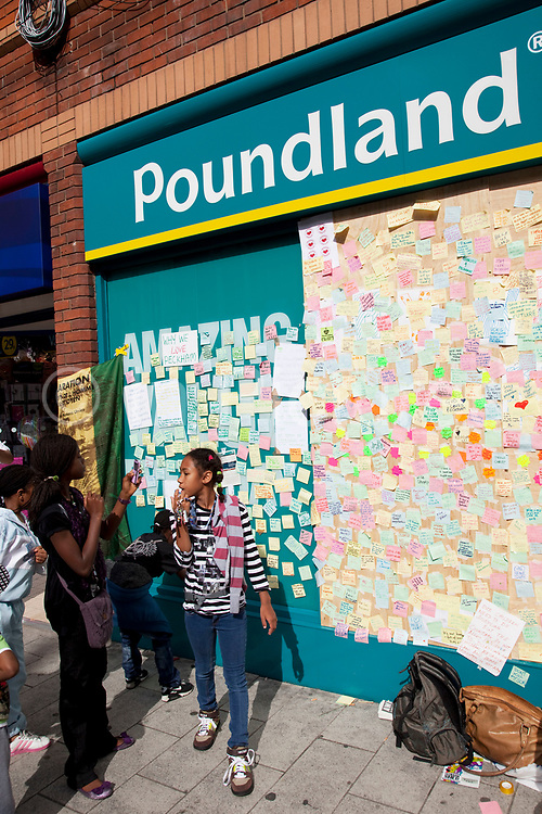People in Peckham, South London place positive messages about love of their community onto a boarded up window of a Poundland shop following the riots. In a week where mobs smashed and looted shops all over the capital, this is a sign of people reacting to send a message to those involved that they stand together with other communities against the unrest. Post-it notes are stuck to this impromptu wall, organised by a few local young people.