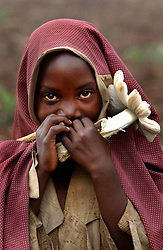 A child holds a mushroom in a village in Rwanda in 2004, ten years after the Rwandan genocide when at least 800,000 ethnic Tutsis and thousands of moderate Hutus in Rwanda were killed.  Despite intelligence provided before the killing began, and international news media coverage of the true scale of violence as the genocide unfolded, most first-world countries including France, Belgium and the United States declined to intervene or speak out against the planned massacres.