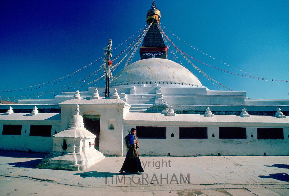 Nepalese woman walking past Bouddhanath Stupa in Nepal at the Kathmandu Valley World Heritage Site.