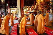Buddhist monks in ochre yellow robes during one of their daily prayer sessions at Longhua Temple in the south of Shanghai, China. This is a working temple where public come to burn incense, offer gifts and to eat. Located on Longhua Road, the temple was first built in 242 AD, during the period of the Three Kingdoms. Longhua Temple is the oldest temple in Shanghai and also the largest at 20,000 square metres including it's grounds. Because of several destructions by the wars, most of the buildings in Longhua Temple were reconstructed during the reign of the Emperor Tongzhi and Guangxu during the Qing Dynasty.