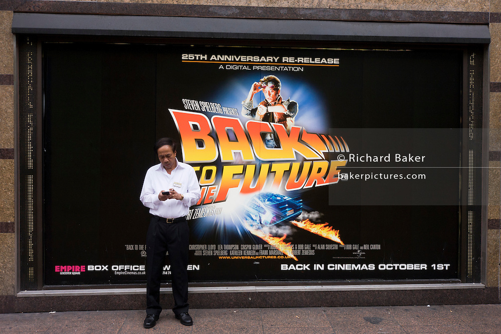Man in street uses his modern mobile phone to type or text with Spielberg's Back to the Future 25th anniversary movie poster