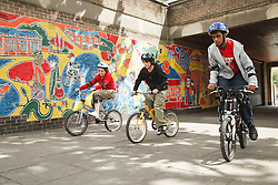 Young people on bikes in front of a mural.