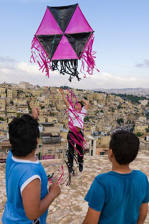 Three boys flying a kite at the Citadel, Amman, Jordan. Photo © Robert van Sluis