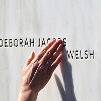 """A visitor to the National Memorial for Flight 93 traces her hand along the letters of Deborah Jacobs Welch's name,  a passenger of Flight 93, at the """" Wall of Remembrance """" on September 11, 2012  near Shanksville, PA.  This is the 11th anniversary of the terrorist attack against the United States.  UPI/Archie Carpenter"""