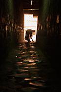 A novice Tibetan Buddhist monk sweeps a dark hallway in a monastery in Shigatse, Tibet (China).