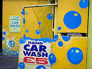 Yellow and blue-theme walls outside a local car wash business in south London. Brightly-painted yellows and blues have been customised on the walls of this local business in south London. A theme of soapy bubbles and a sign selling £5 washes advertises this business located in a Victorian railway arch where many businesses work from.